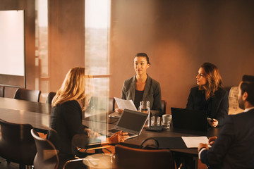 Legal colleagues planning over laptops and documents at conference table in law office