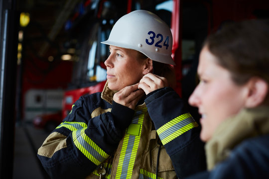 Female firefighter wearing helmet while standing with coworker in fire station