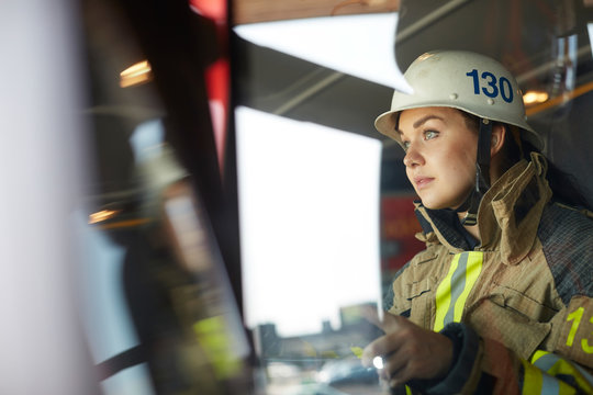 Confident female firefighter sitting in fire engine