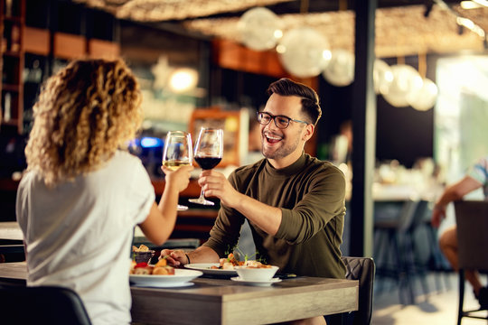 Cheerful couple toasting with wine during lunch time in a restaurant.