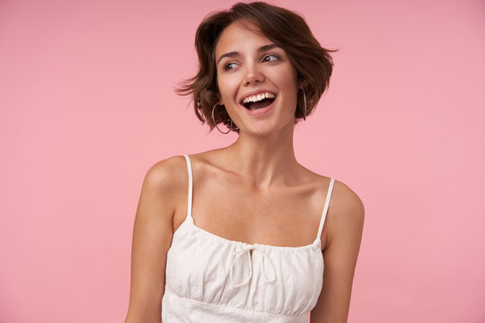 Studio shot of charming young female with casual hairstyle wearing white top while standing over pink background, looking aside cheerfully and smiling widely, being in nice mood