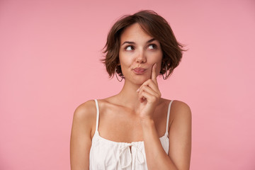 Indoor photo of lovely young brunette female with casual hairstyle wearing white top while standing over pink background, looking aside thoughtfully and rasing eyebrow