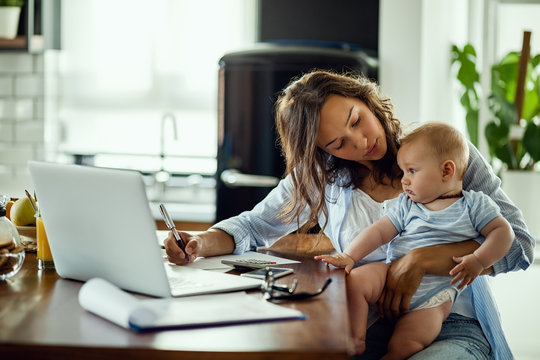 Young mother working on home finances and talking to her baby son.