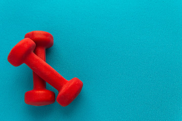 Red dumbbells on a blue fitness mat