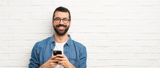 Handsome man with beard over white brick wall sending a message with the mobile