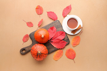 Beautiful autumn composition with pumpkins, cup of tea and leaves on color background