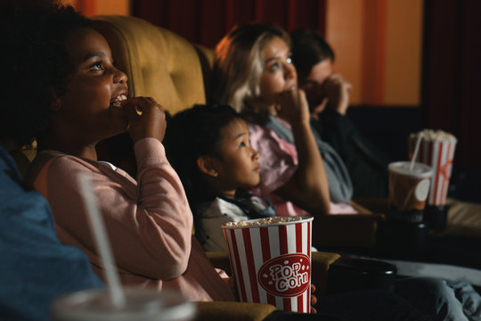 diversity people children and young people having fun watching movie and eating popcorn in cinema theater