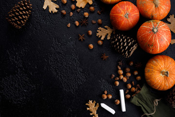 Autumn frame of pumpkins, tree leaves, hazelnuts on a black textural background. Crayons for drawing. Autumn, fall, thanksgiving concept. Flat lay, copy space.