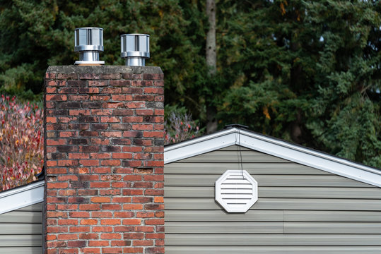 Exterior wall of suburban house, old brick chimney with chimney vents, attic fan exhaust vent on wall