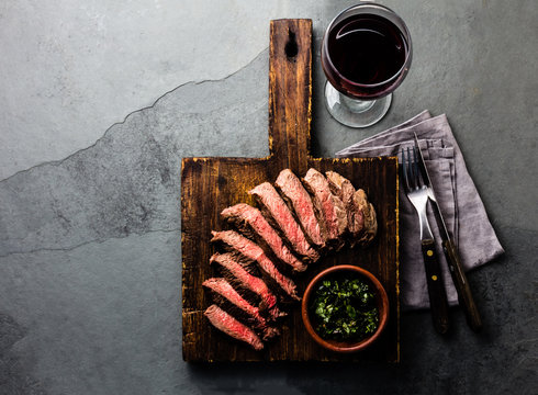 Slices of beef medium rare steak on wooden board, glass of red wine