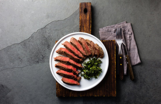 Medium beef steak on white plate, slate background