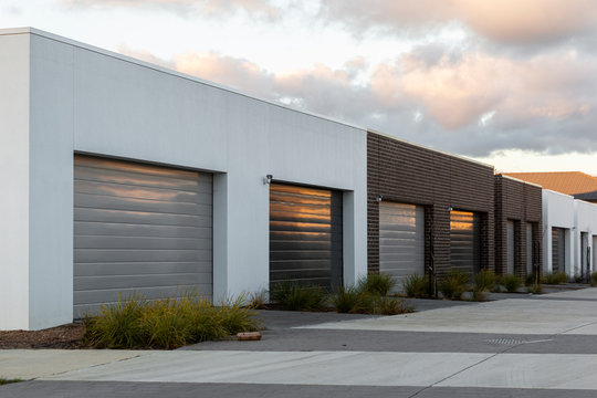 Modern car garages reflecting golden afternoon light in suburban area.