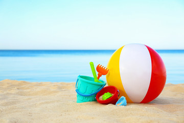 Set of plastic beach toys and colorful ball on sand near sea. Space for text