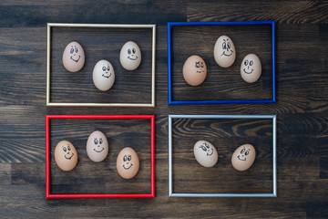 Picture frame and many funny eggs smiling on dark wooden wall background. Eggs family emotion face portrait. Concept funny food