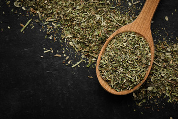 herbs of Provence seasoning for food in wooden spoon and black background isolated. macro shot