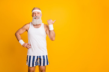 Photo of cheerful positive confident old man pointing at empty space with his thumb smiling toothily holding hand on waist in striped shorts isolated vivid yellow color background