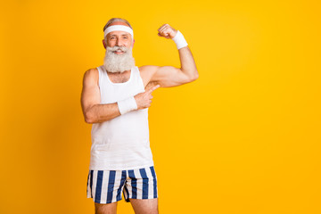 Photo of cheerful positive toothy beaming man pointing at his biceps to show results of his work isolated vivid yellow color backgroun Fototapete