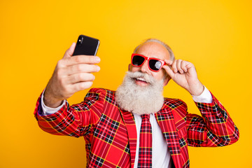 Close-up portrait of his he nice handsome attractive cheerful cheery grey-haired man macho touching specs taking making selfie isolated over bright vivid shine vibrant yellow color background