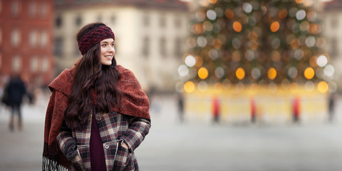 Beautiful joyful woman portrait in a city. Smiling  girl wearing warm clothes and hat  in winter or autumn. Christmas time with  unfocus lights on backgrounde. Copy space