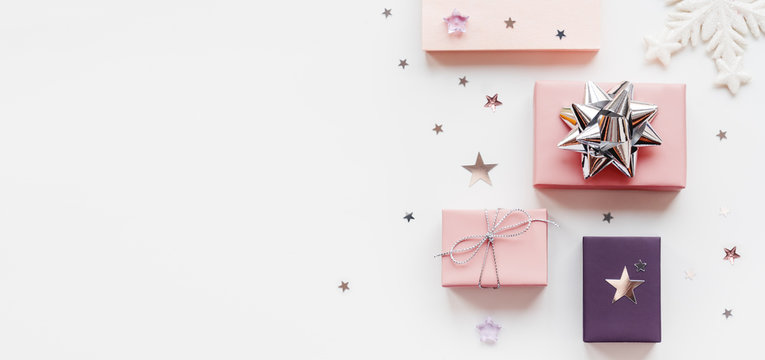 Banner with holiday presents. Gifts wrapped in pale pink and violet paper with silver ribbons and bow. Stars confetti and white copy space. Top view, flat lay.
