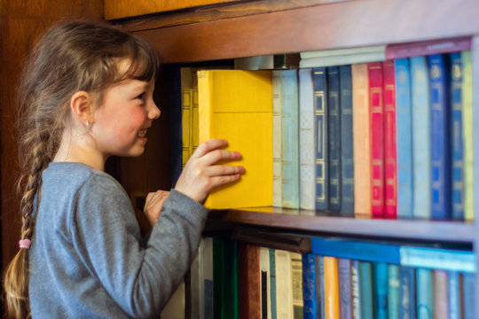 The child gets a textbook with wooden shelf of the old library. A little girl is taking a yellow book from a bookshelf. Children's educational concept.