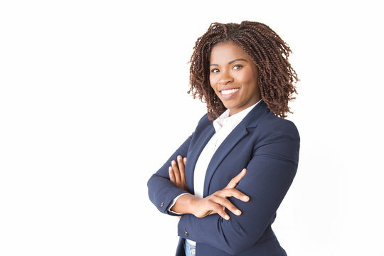Happy successful female professional smiling at camera. Young African American business woman with arms crossed standing isolated over white background. Confident businesswoman concept