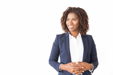 Happy female business leader posing with clasped hands. Young black business woman standing isolated over white background, looking at copy space away, smiling. Advertising concept Wall mural