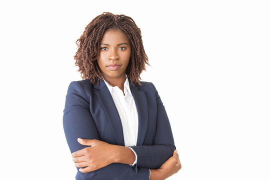 Serious confident female business leader looking at camera. Young African American business woman with arms crossed standing isolated over white background. Young professional concept