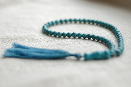 long blue  turquoise prayer beads for praying on light background