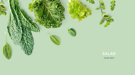 Creative layout made of kale, salad leaves, spinach, ruccola on green background. Flat lay. Food concept. Macro concept.
