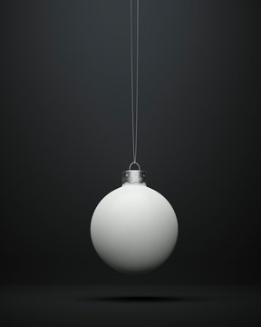 Matte white Christmas ball hanging centered on a black background.