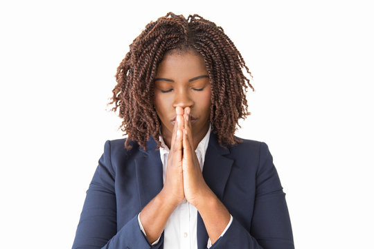 Peaceful female employee praying with closed eyes. Young African American business woman making pray gesture, keeping hands at mouth. Praying concept