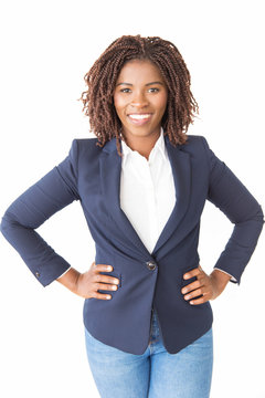 Happy female business leader posing with hands on hips. Young African American business woman standing isolated over white background, looking at camera, smiling. Successful businesswoman concept