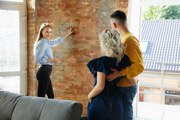Wall Mural - Interior designer working with young couple. Lovely family and professional designer or architector discussing conept of future interior, working with colour palette, room drawings in modern office.