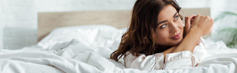 panoramic shot attractive woman lying in bed at morning