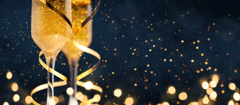 Two glasses of champagne with golden confetti, glitter, serpentine and lights.