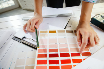 Wall Mural - Professional interior designer or architector working with colour palette, room drawings in modern office. Young female model planning future flat or house, choosing colors and derocation.