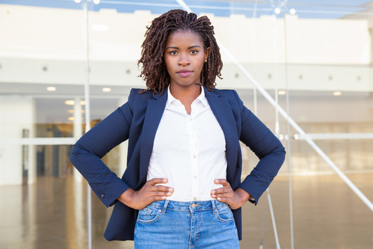 Serious successful female manager posing near office building. Young African American business woman standing outside, keeping hands on hips, looking at camera. Female business portrait concept