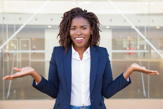 Cheerful confused female manager posing outside. Young black business woman standing near outdoor glass wall, looking at camera, shrugging. Doubt or question concept