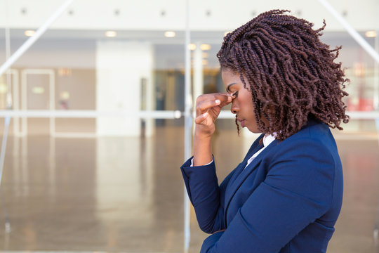 Serious upset female employee thinking over bad news outside office. Young African American business woman standing at glass wall with head low, touching face, looking into vacancy. Bad news concept
