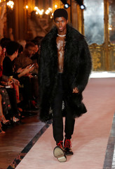 A model wears a long black fake fur coat over black trousers at the at the Giambattista Valli fashion show, where the designer presented his collection created in collaboration with fast-fashion giant H&M, in Rome