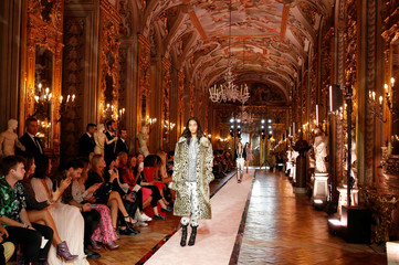 A model walks on catwalk wearing a leopard-effect fake fur coat during fashion show to present creations of designer Giambattista Valli and fast-fashion giant H&M in Rome