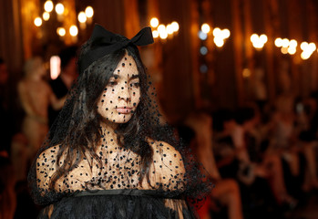 A model walks on catwalk wearing a black tulle dress during fashion show to present creations of designer Giambattista Valli and fast-fashion giant H&M