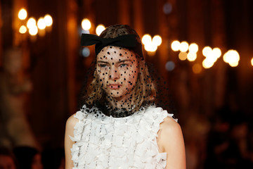 A model wears a black veiled fascinator with bow and a sleeveless white silk adorned top, at the Giambattista Valli fashion show, where the designer presented his collection created in collaboration with fast-fashion giant H&M, in Rome