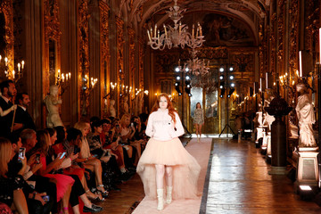 Plus-size model walks on catwalk wearing a short-fronted, long-back pink tulle dress during fashion show to present creations of designer Giambattista Valli and fast-fashion giant H&M