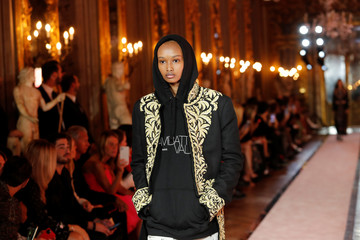 A model walks down the catwalk wearing a hooded black jumper with gold decorations and a white logo at fashion show to present creations of designer Giambattista Valli and fast-fashion giant H&M in Rome