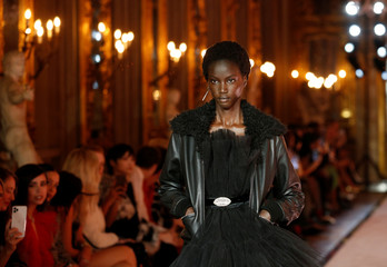 A model walks on catwalk wearing a black dress during fashion show to present creations of designer Giambattista Valli and fast-fashion giant H&M in Rome