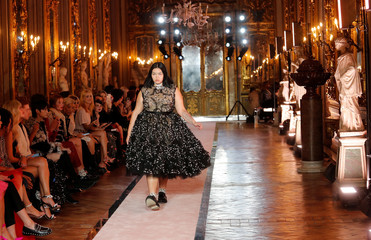 A plus-size model walks down the catwalk wearing a black tulle embroidered dress during the fashion show to present creations of designer Giambattista Valli and fast-fashion giant H&M in Rome