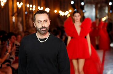 Designer Giambattista Valli walks on catwalk followed by U.S. model Kendall Jenner during a fashion show to present his creations for a collaboration with fast-fashion giant H&M