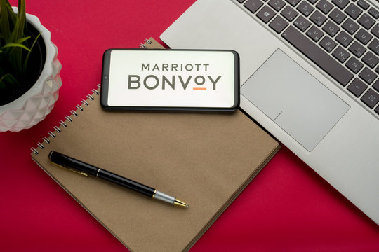 Tula, Russia - october 19, 2019: Marriott International Bonvoy displayed on a smartphone near modern laptop on red background